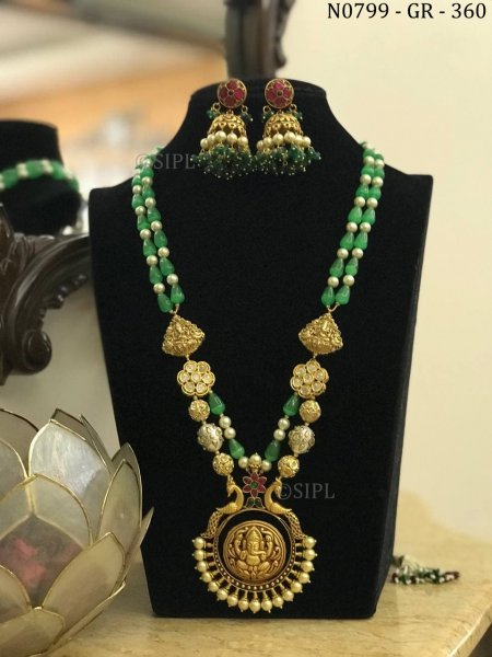 This temple Jewelry has Lord Ganpati , seated on a lotus, and flanked by peacock on both sides.